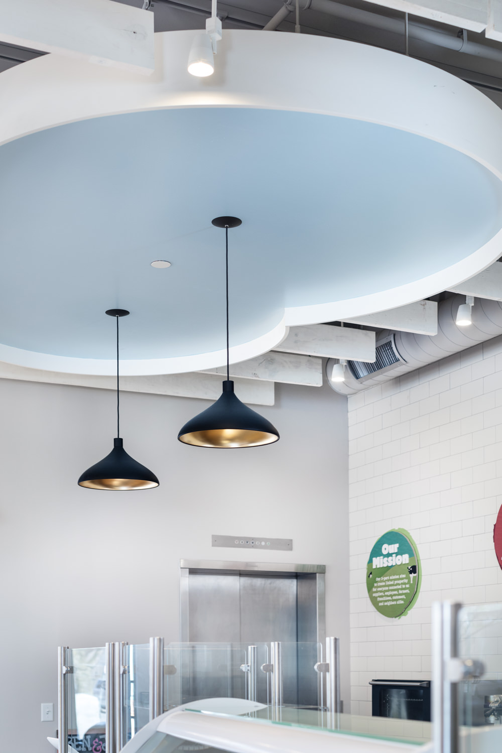 Photo of black pendant lights hung from a cloud shaped bumpout in the cileing of the 2017 renovation of the Ben & Jerry's scoop shop on Church Street in Burlington Vermont taken by photographer Stina Booth