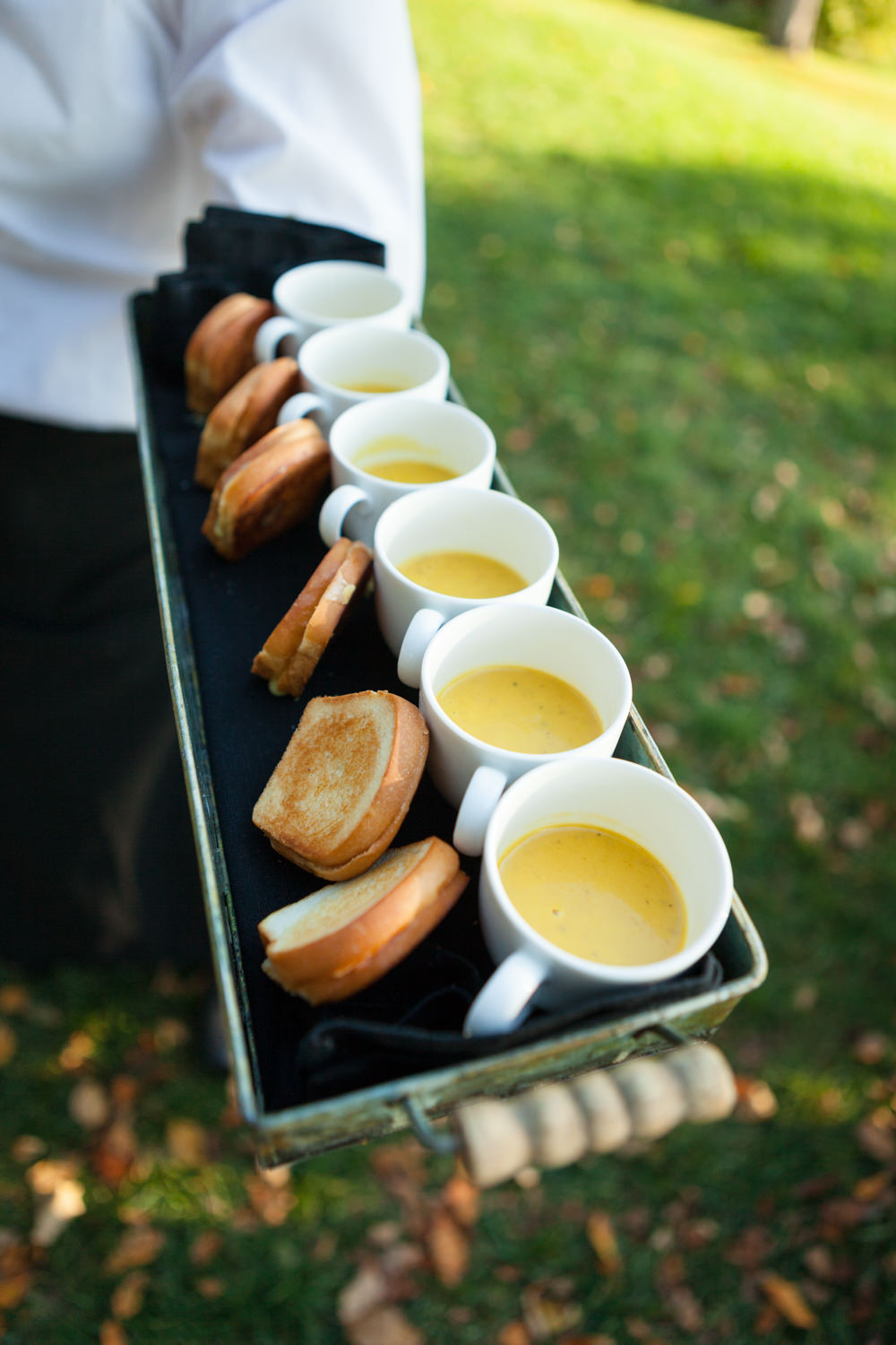 Mini ladles of a squash soup are served with tiny grilled cheese sandwiches on an hors d'oeuvres tray in a photo by food photographer Stina Booth