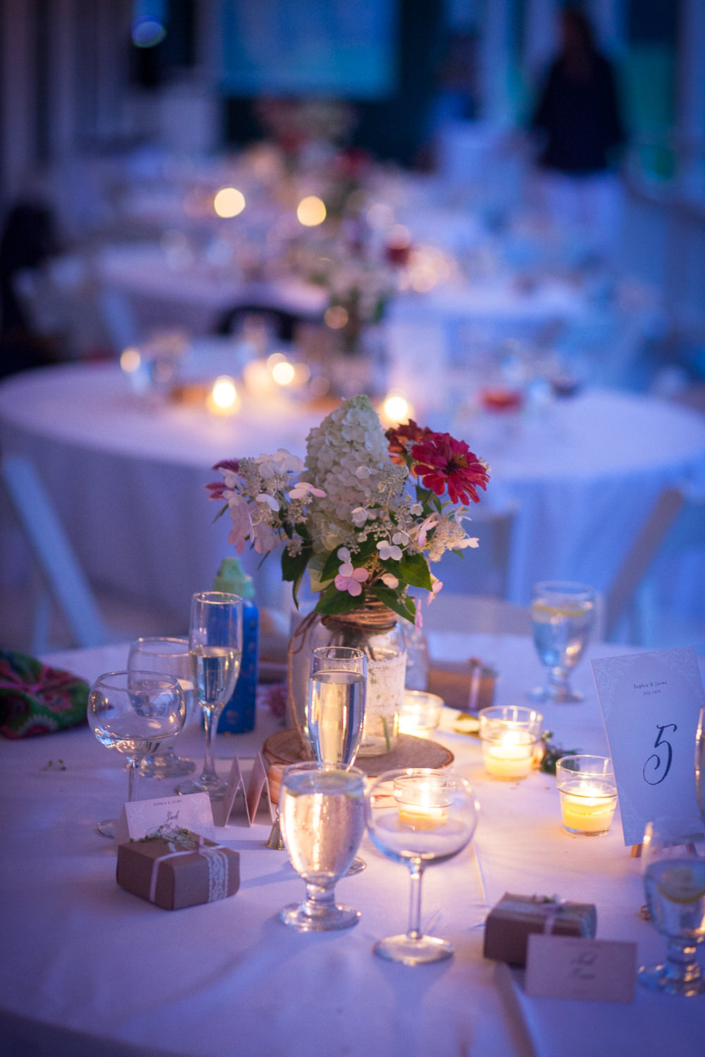 Tea lights illuminate a wedding tablescape at dusk at the Grand Isle Lake House in Vermont by food photographer Stina Booth