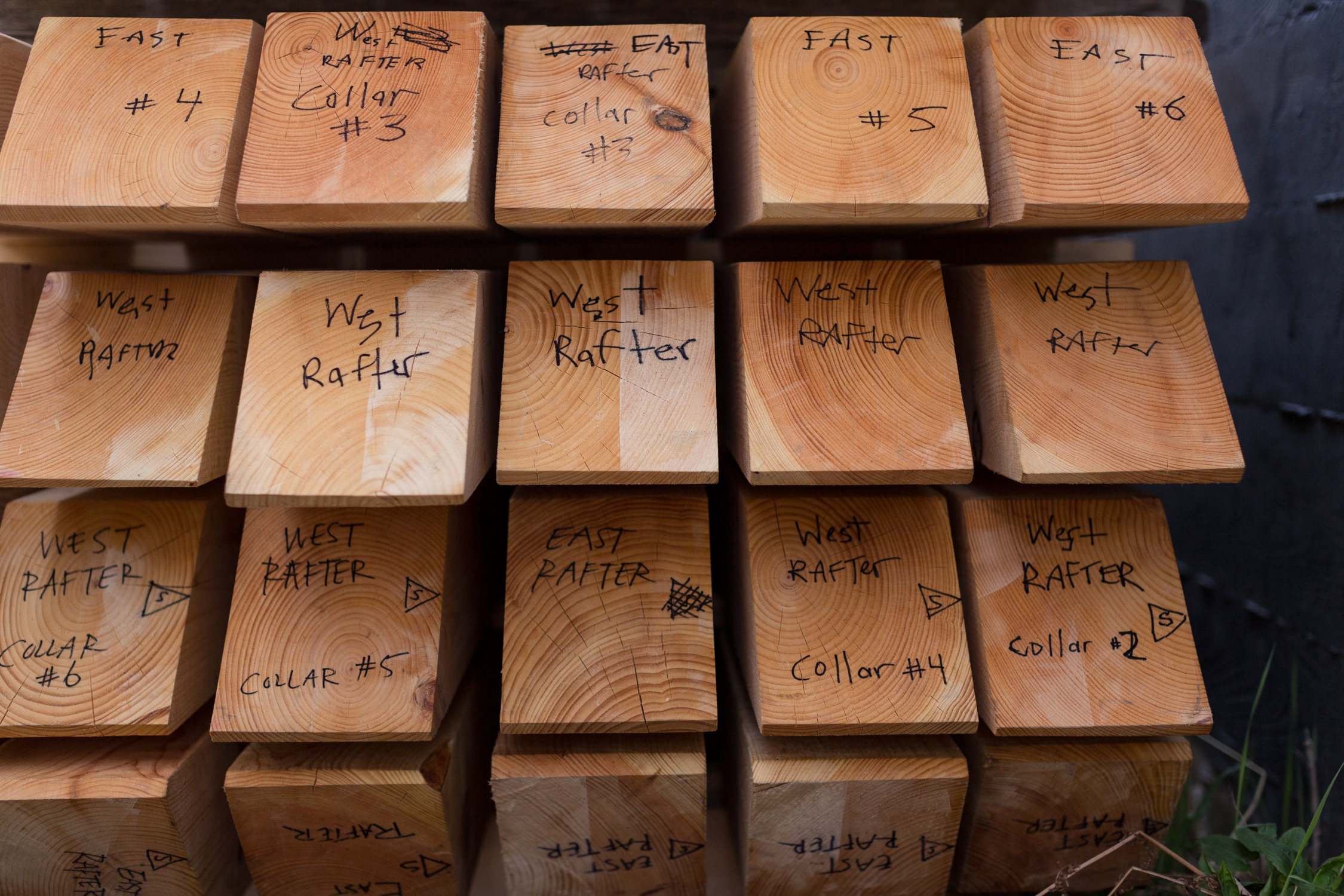 Detail photo of numbered beams ready for a timber frame home construction taken by Vermont professional photographer Stina Booth