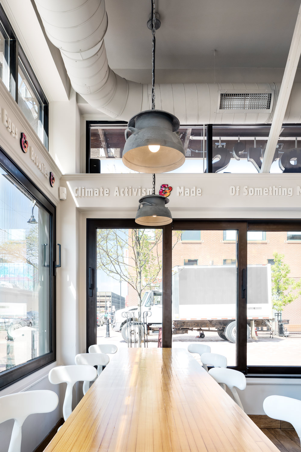 Photo of customer seating with custom milk can light pendants in the 2017 renovation of the Ben & Jerry's scoop shop on Church Street in Burlington Vermont taken by photographer Stina Booth