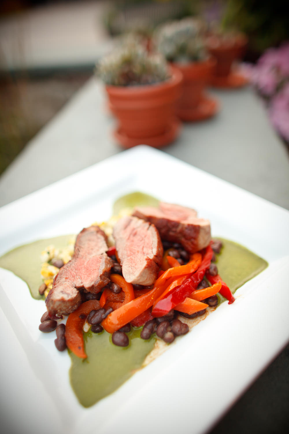 Seared filet mignon on top of a heap of black beans and red pepper strips from the Timbers Restaurant at the Sugarbush Resort in Vermont photographed by food photographer Stina Booth