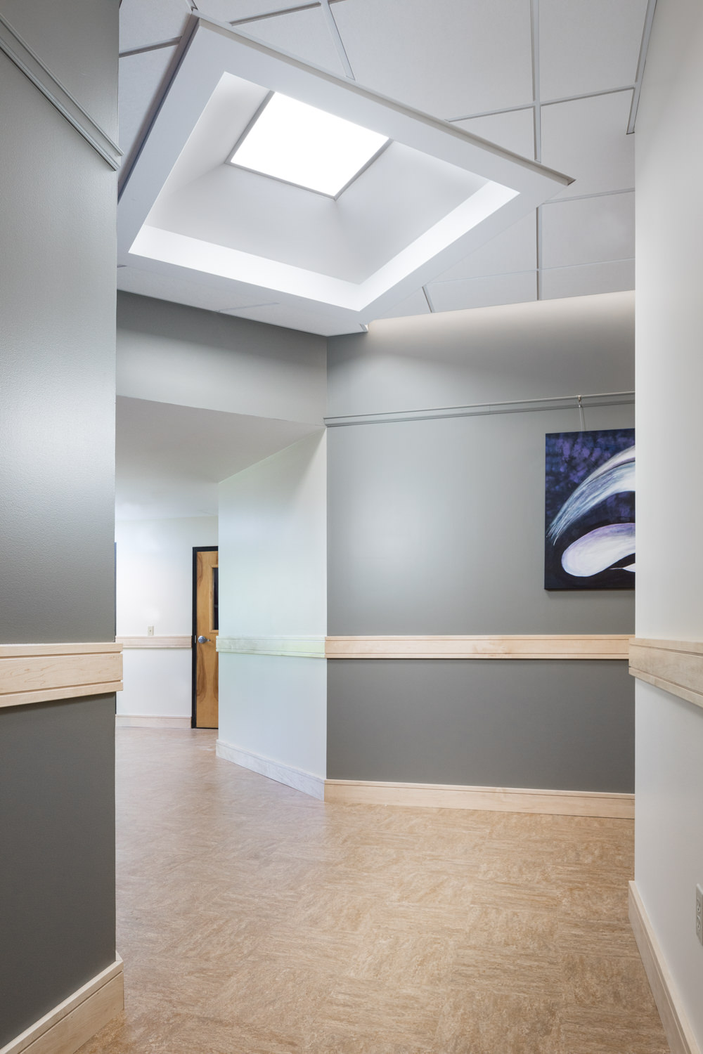 Photo of the naturally lit hallway featuring gray walls and skylight in the Biotek facility in Winooski Vermont by photographer Stina Booth