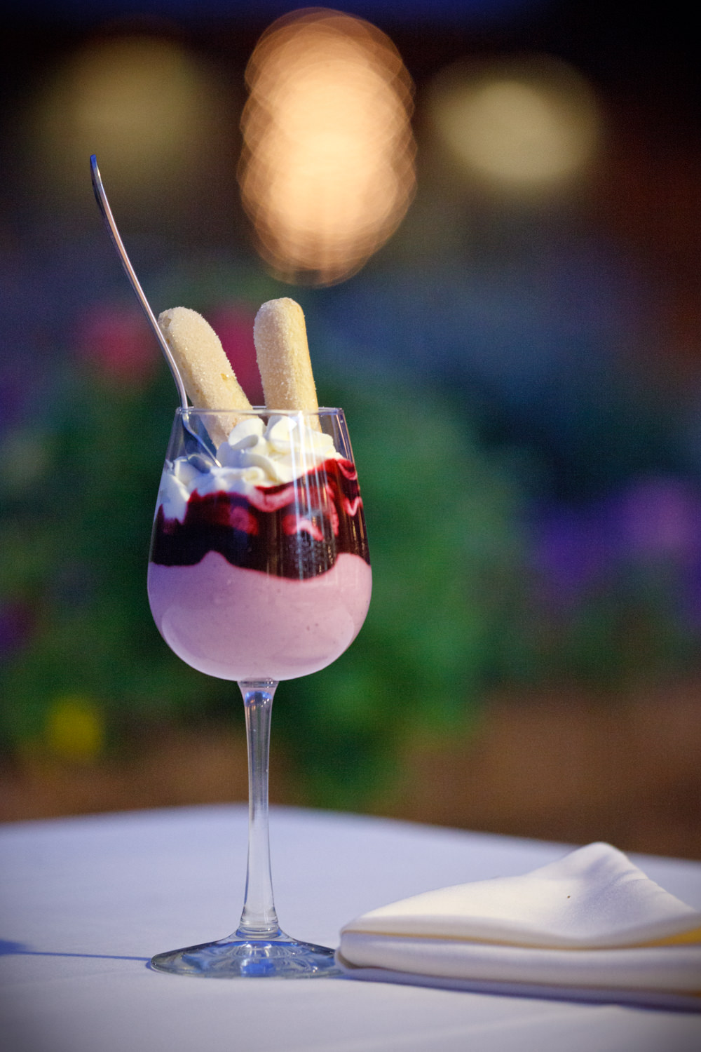 A whipped mousse dessert topped with whipped cream and lady fingers is served in a wine glass in a photo be Vermont food photographer Stina Booth