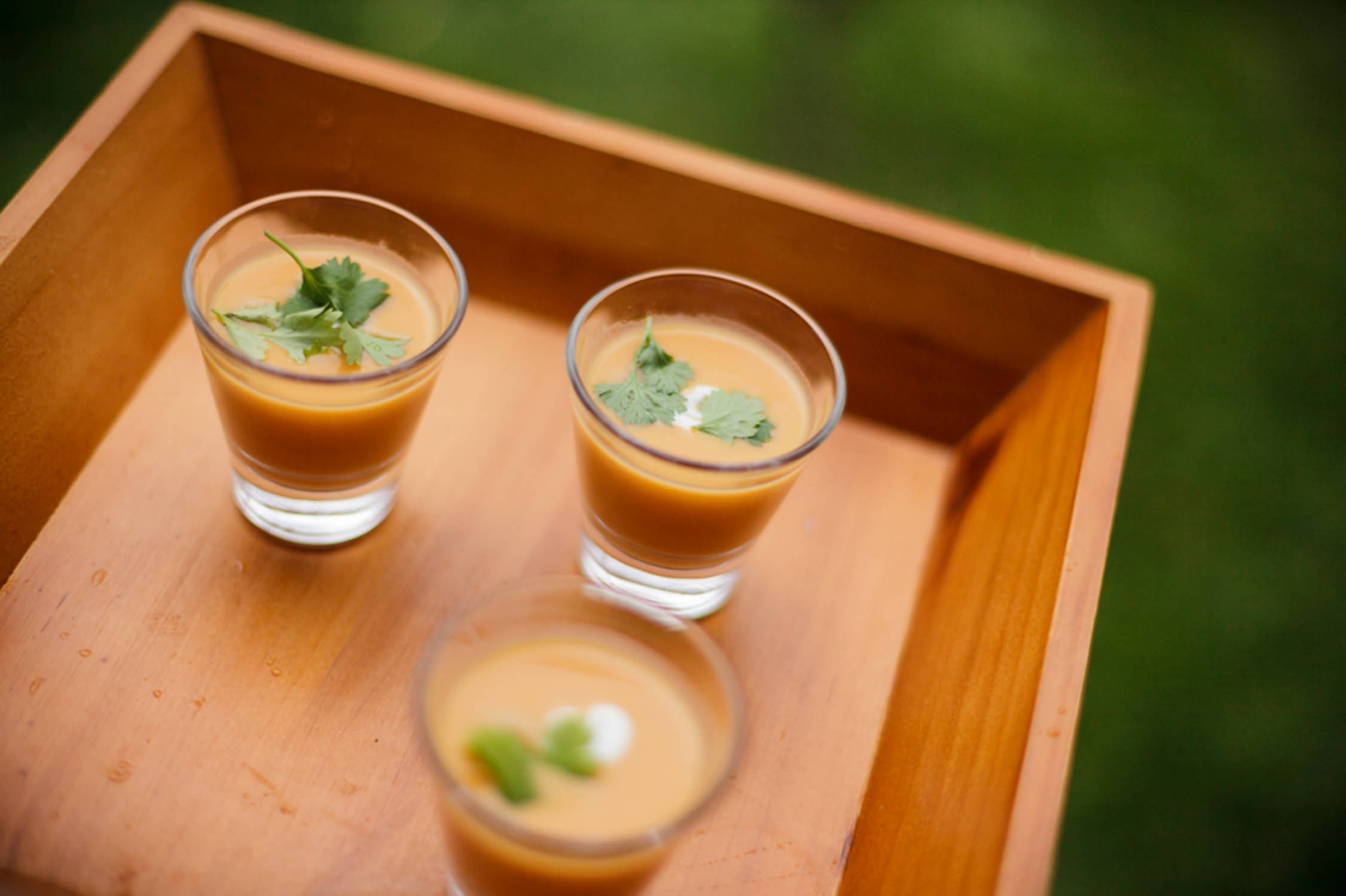 A photo of soup served in shot glasses on a bamboo serving tray by Vermont food photographer Stina Booth