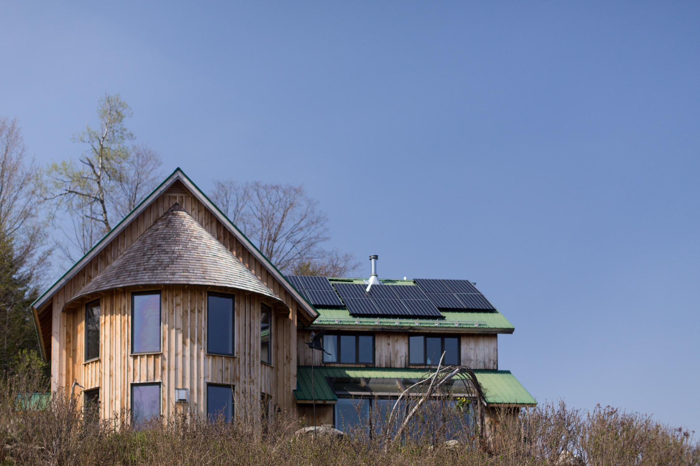 A view of the round straw cell kitchen addition of a Marshfield Vermont home by Stina Booth architecture photography