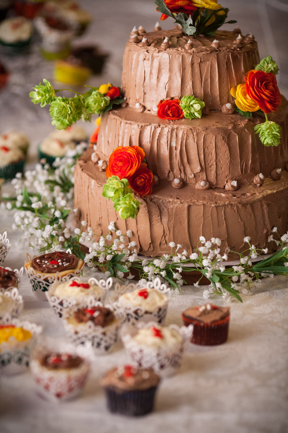 A photo of a chocolate cake adorned with red flower details and surrounded by a table of cupcakes by food photographer Stina Booth