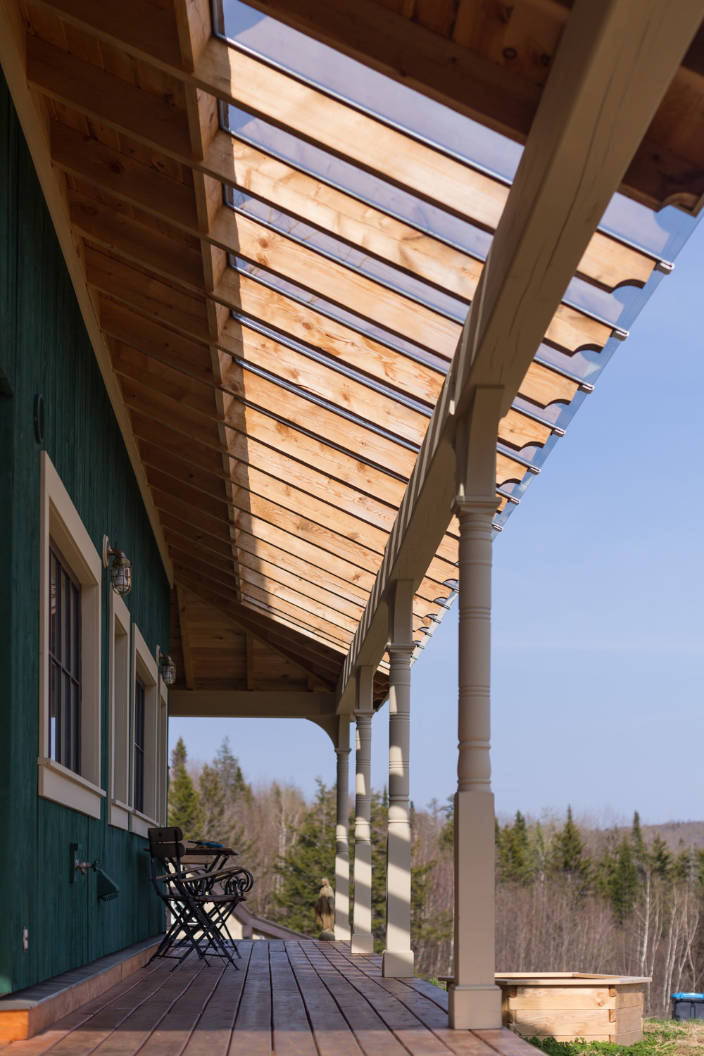 A view of pergola roof on the porch of a Central Vermont farmhouse designed by New Frameworks Natural Building taken by architecture photographer Stina Booth
