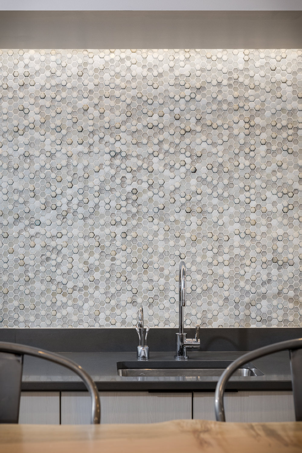 Detail photo of the modern hex wall tile, undermount stainless steel sink, industrial stools and raw edge wood table in the employee lunch room at KPMG in Vermont taken by professional photographer Stina Booth