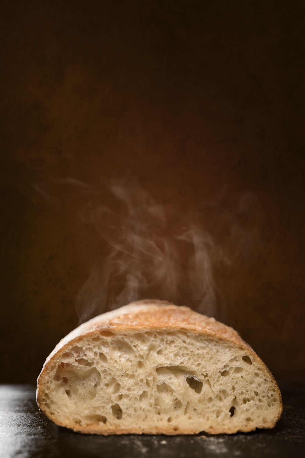 Steam rises from a fresh loaf of sourdough bread seen sliced open