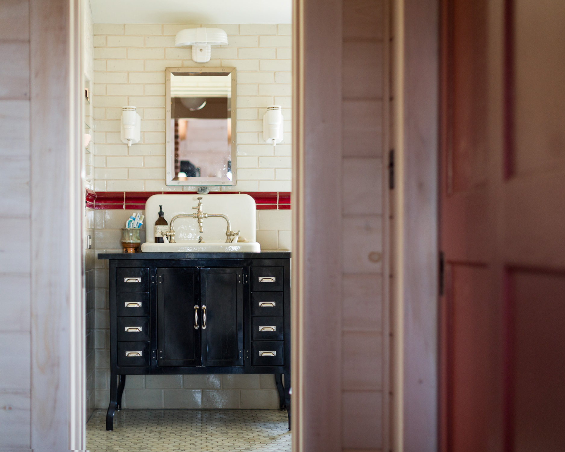 A view through the doorway into a farmhouse bathroom with a vanity mounted sink taken by architecture photographer Stina Booth