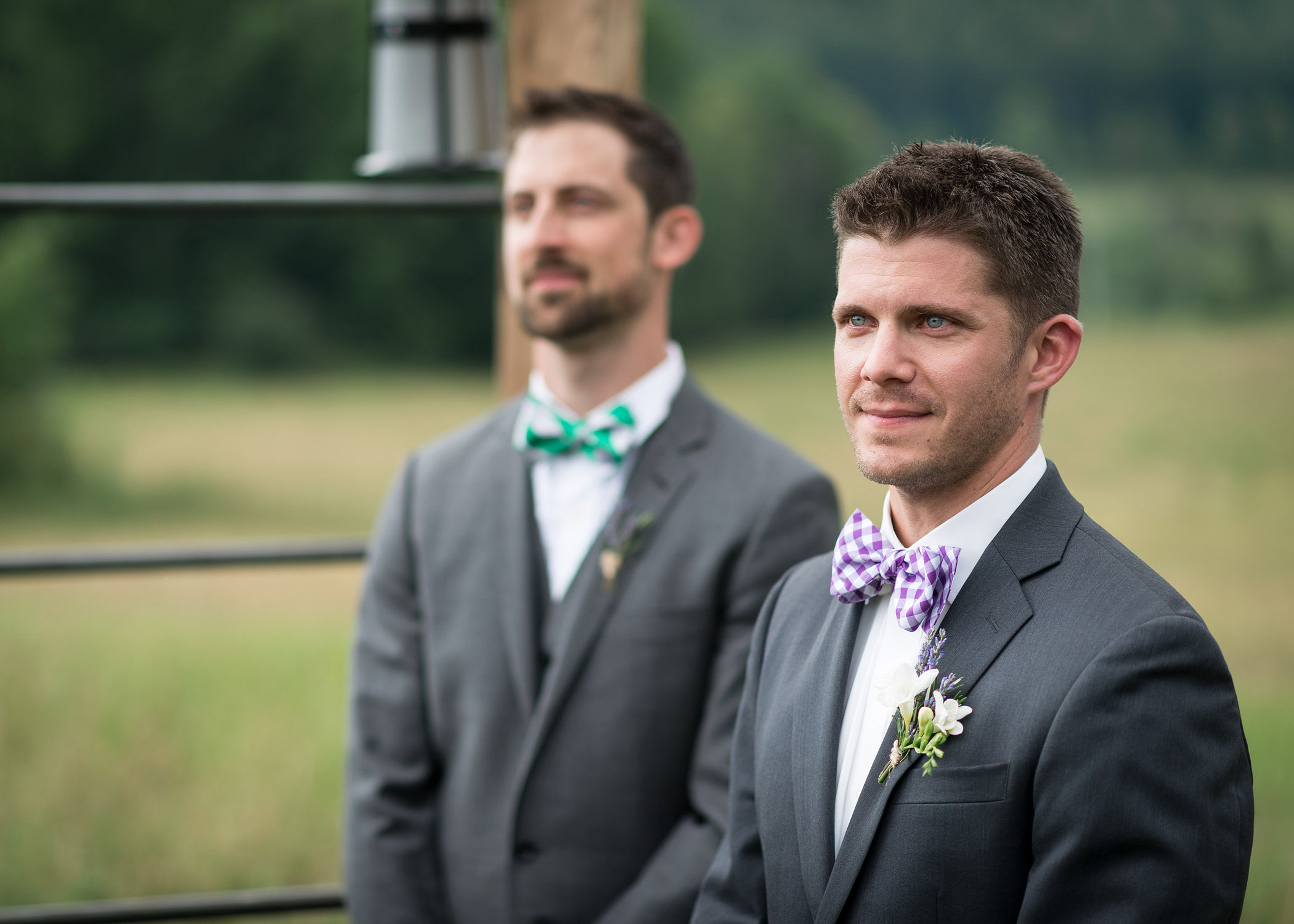 A groom watches his bride walk down the aisle during a wedding at Bliss Ridge taken by Vermont wedding photographer Stina Booth