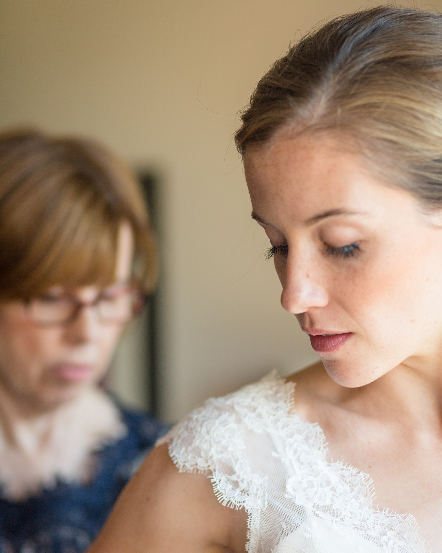 A mother helps the bride get dressed before her wedding by Vermont photographer Stina Booth