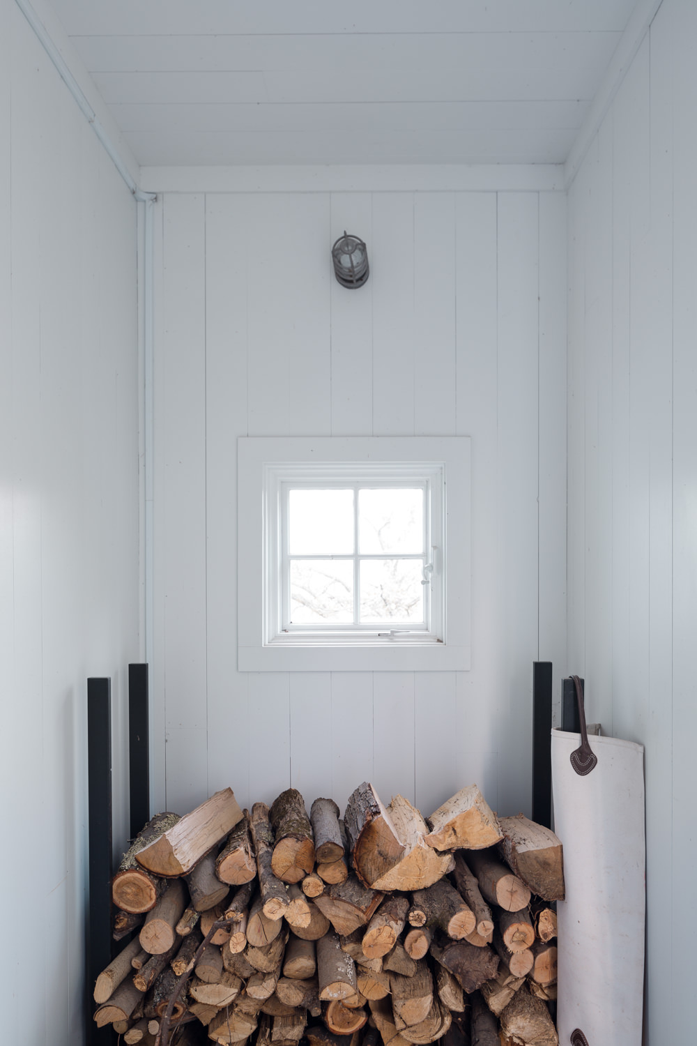A stacked woodpile in the entrance to a contemporary Vermont home by Stina Booth