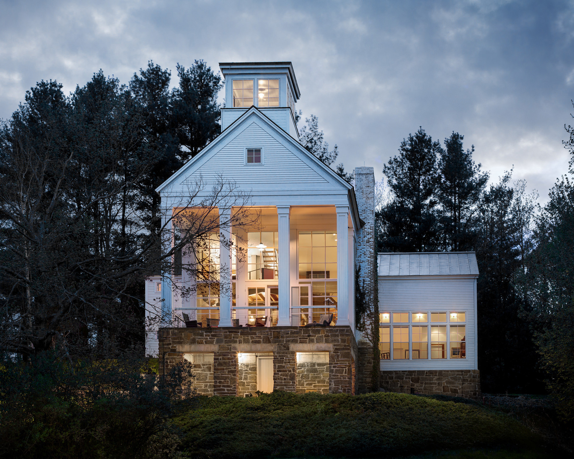 An exterior view at twilight of a traditional Vermont home by professional photographer Stina Booth