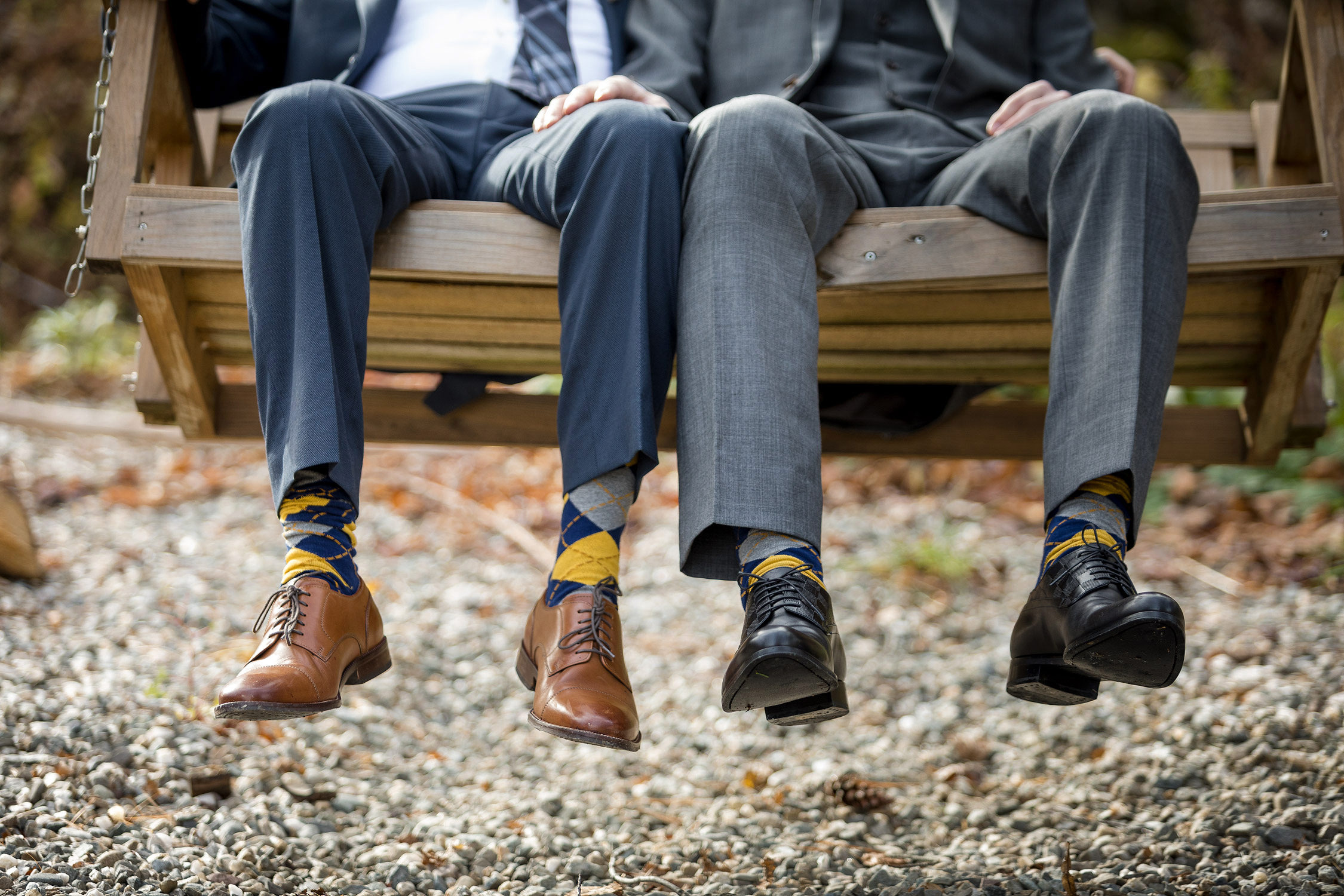 The feet of a gay couple sitting together on a wooden swing