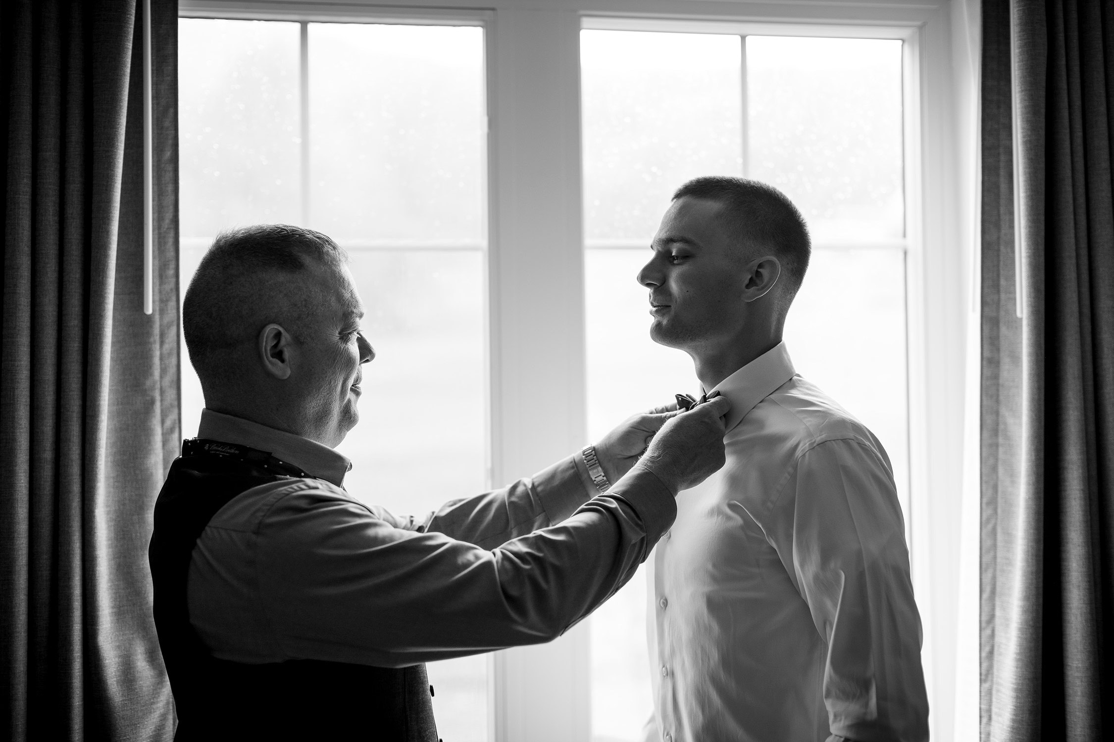 A photo of the groom's father helping him with his bowtie before a Jay Peak Resort wedding by Vermont photographer Stina Booth