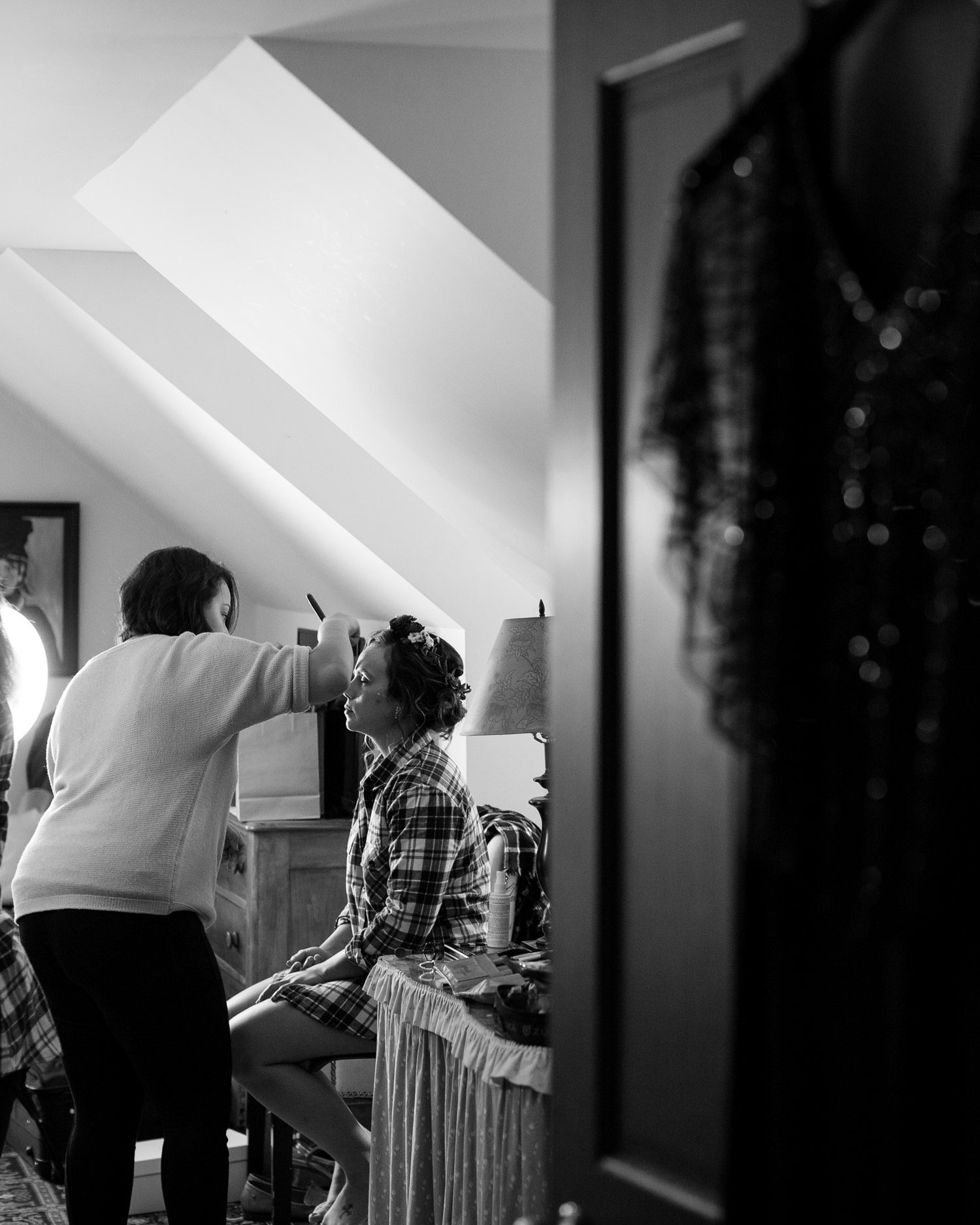 A bride getting eye making applied at the Alerin Barn in St. Johnsbury before her wedding by Vermont photographer Stina Booth