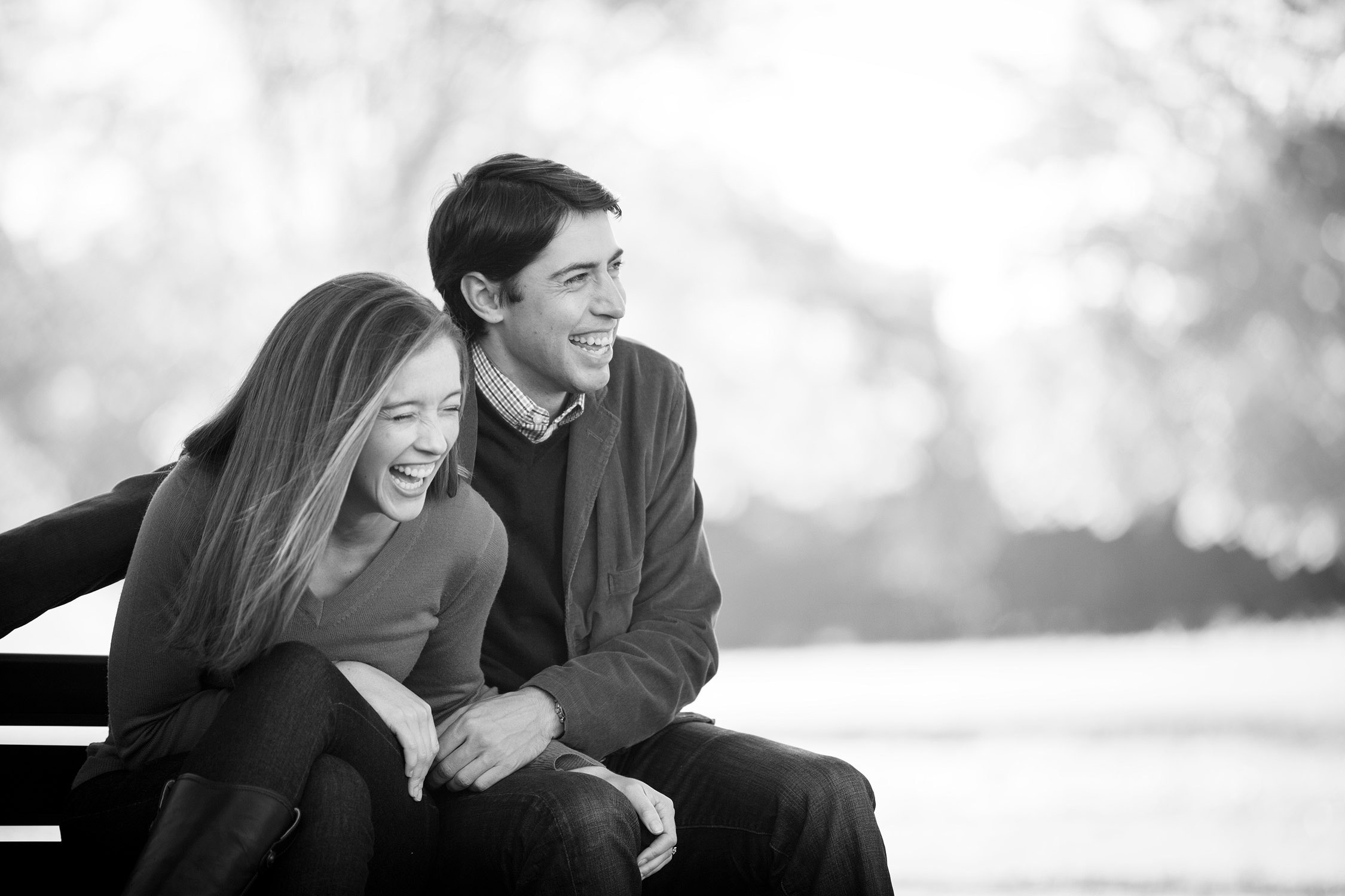 A couple laughs hysterically while sitting on a bench at All Souls Interfaith Gathering during an engagement session by Vermont wedding photographer Stina Booth
