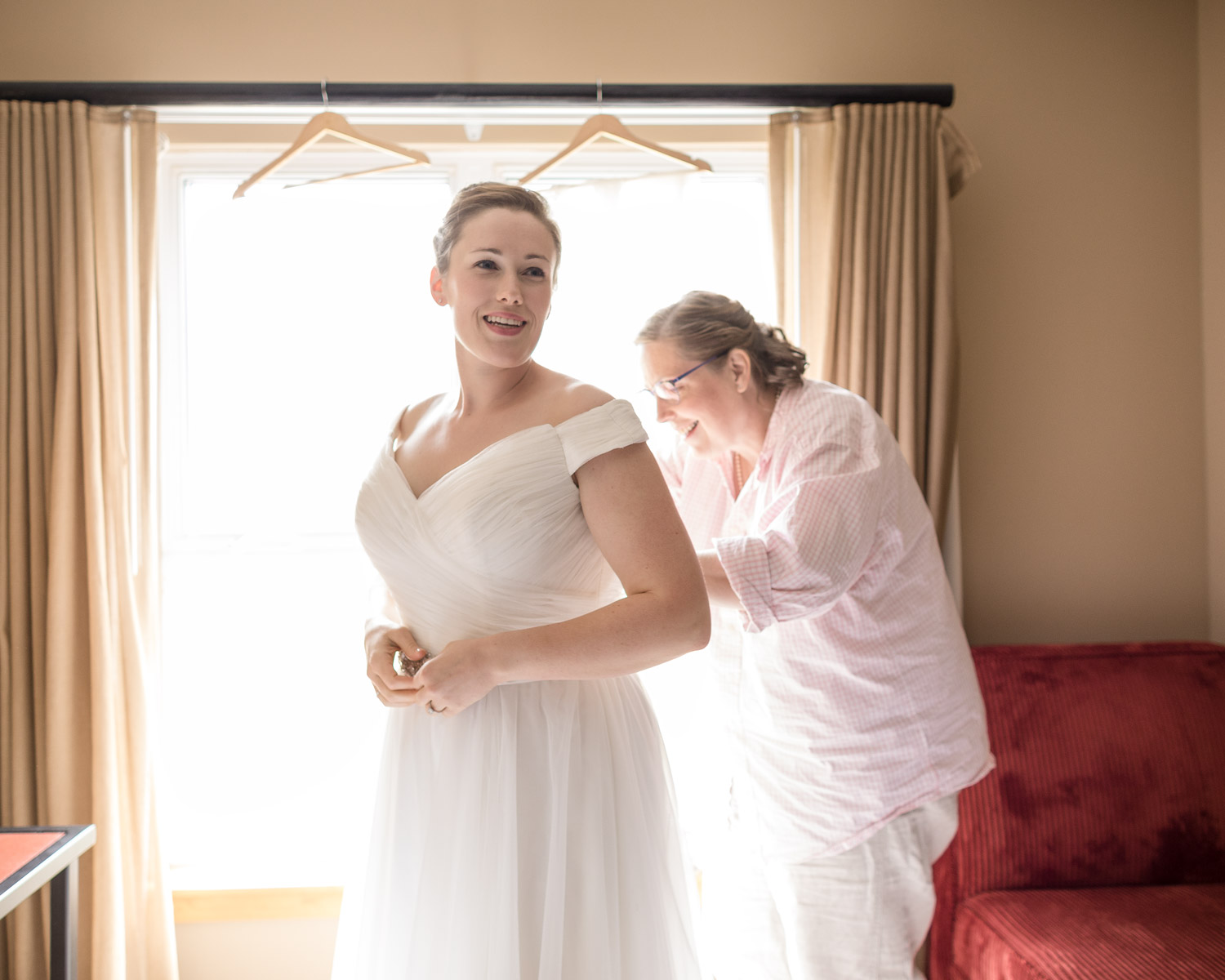 A bride's mother helps her get her wedding gown on before her Jay Peak wedding by Vermont photographer Stina Booth