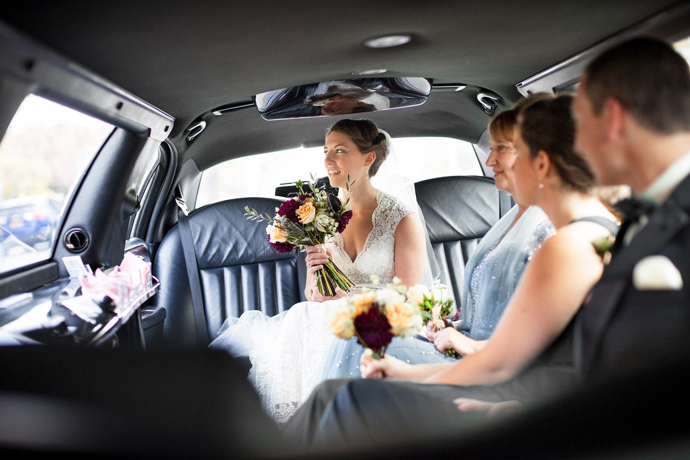 A bride waits in the limo before a church ceremony on Burlington Vermont in a photo by wedding photographer Stina Booth