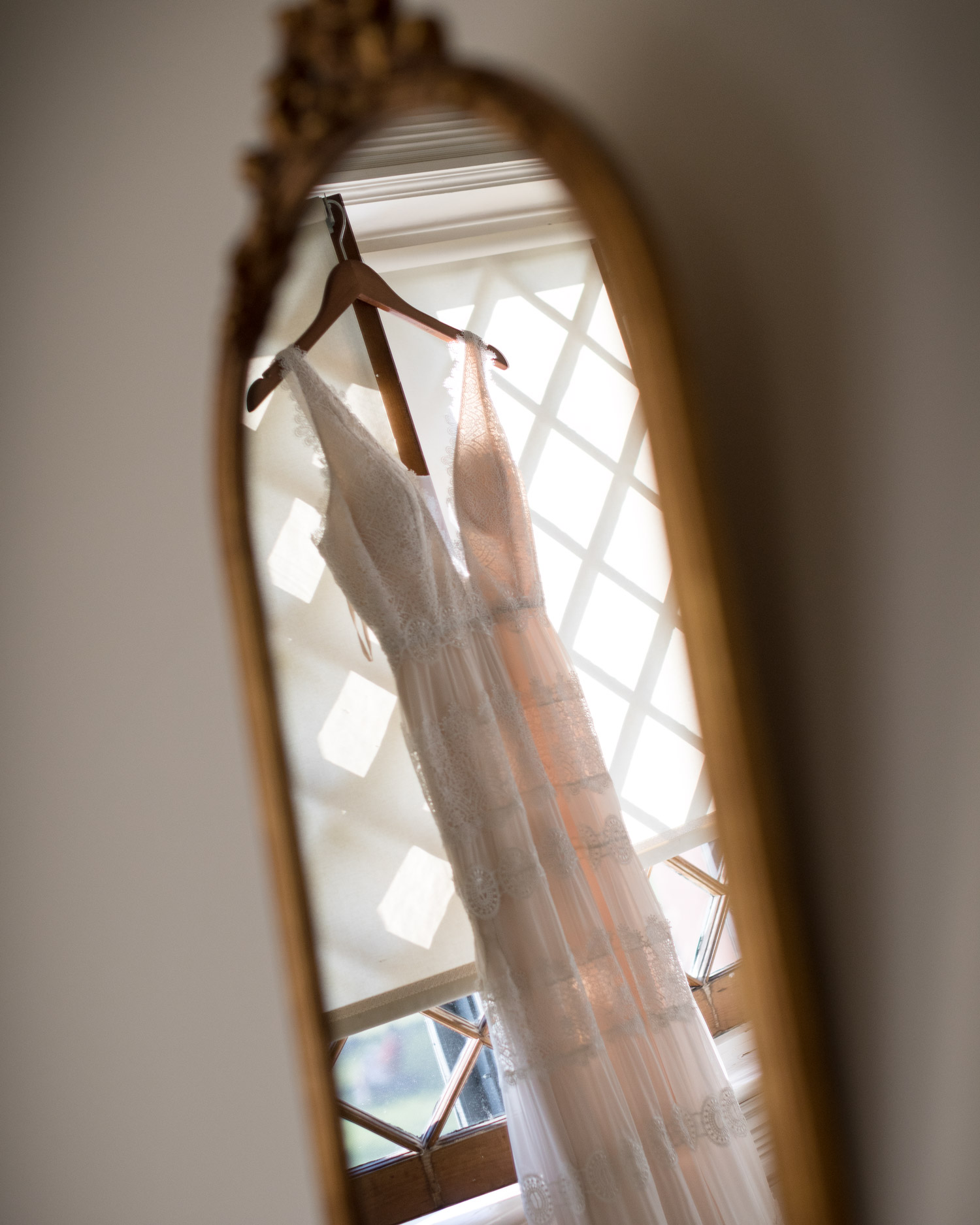 A lace wedding gown hanging in a window is reflected in an antique mirror in a guest room at the Inn at Shelburne Farms in a photo by wedding photographer Stina Booth
