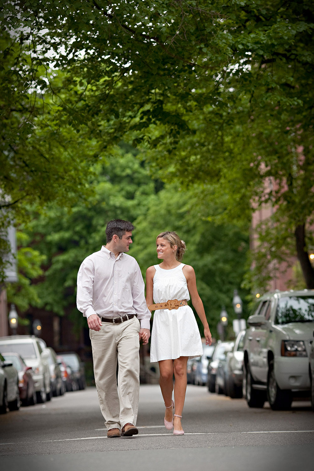 A couple walks hand in hand down a tree lined street in Boston during an engagement session by by Vermont wedding photographer Stina Booth