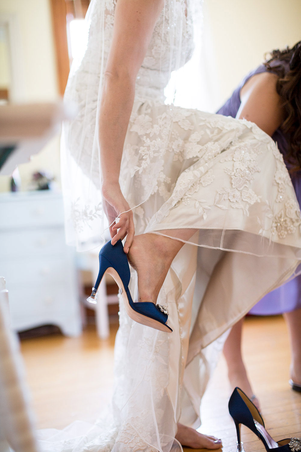 A bride putting on a navy blue high heel shoe