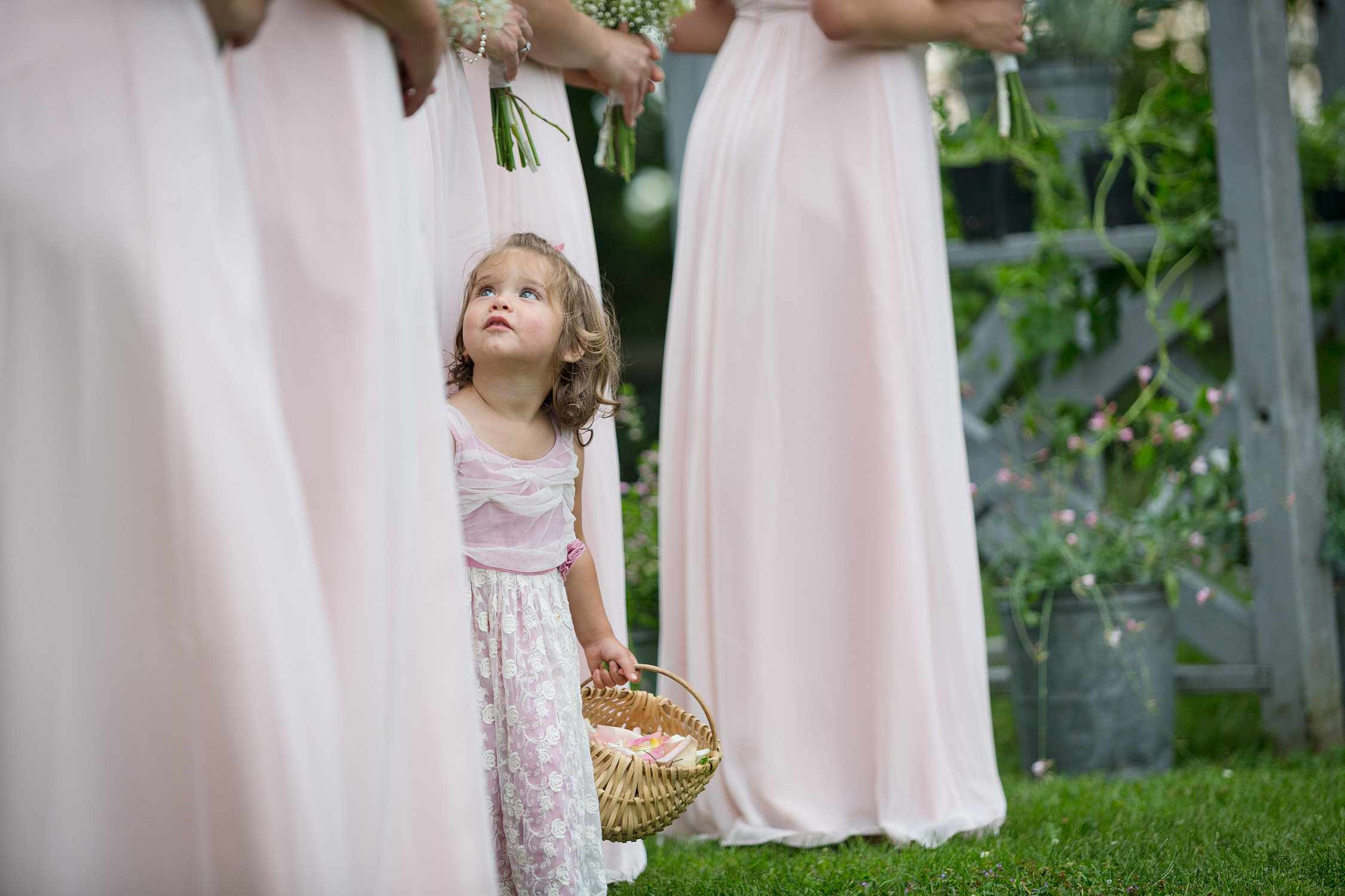 A flower girl peeks up between the dresses of the bridesmaids during a ceremony at the Grand Isle Lake House by Vermont wedding photographer Stina Booth