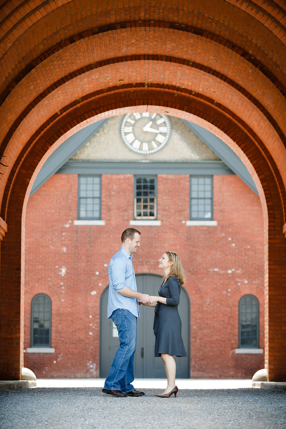 A couple poses under the brick arch of a building at Shelburne Farms during an engagement session
