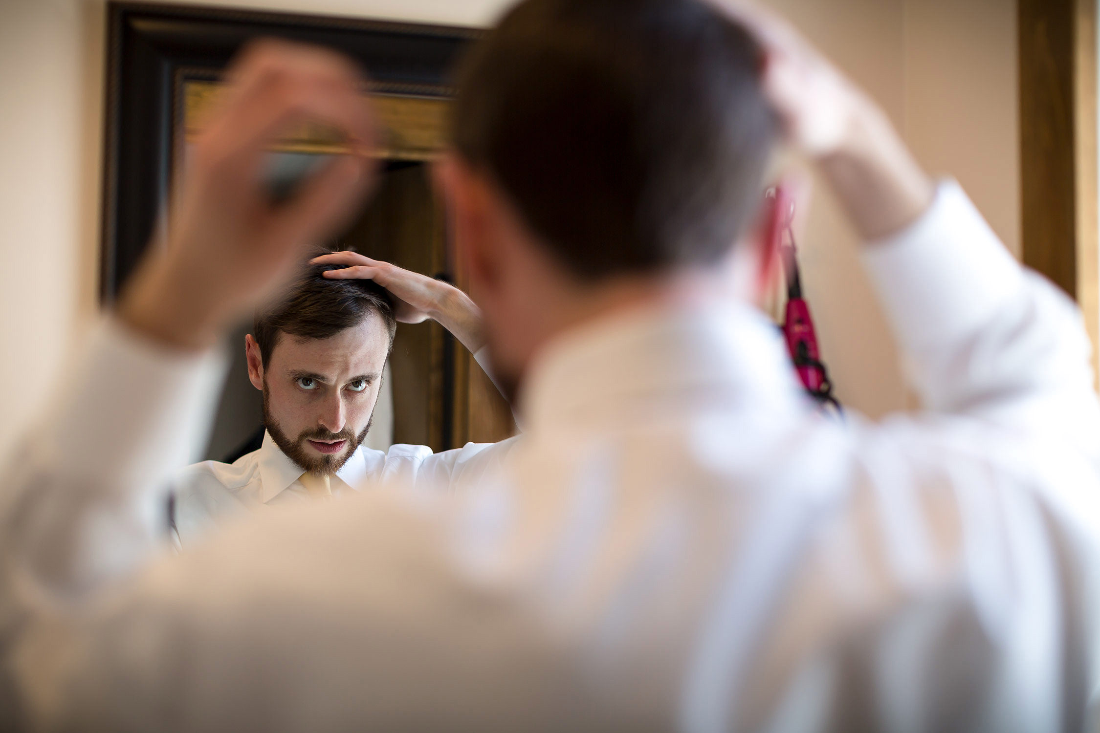 Photo by Vermont wedding photographer Stina Booth of a groom fixing his hair in a mirror