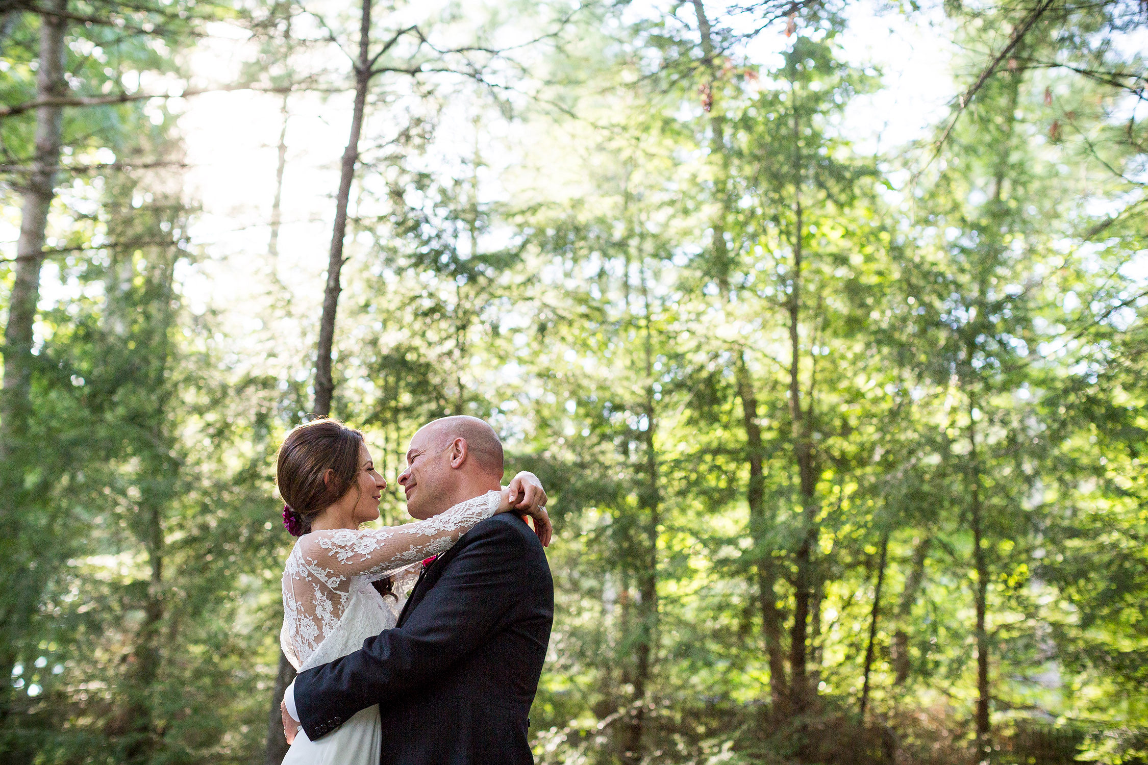 Photo by Vermont wedding photographer Stina Booth of a couple embracing in a portrait in the woods of Woods Hollow in Westford Vermont