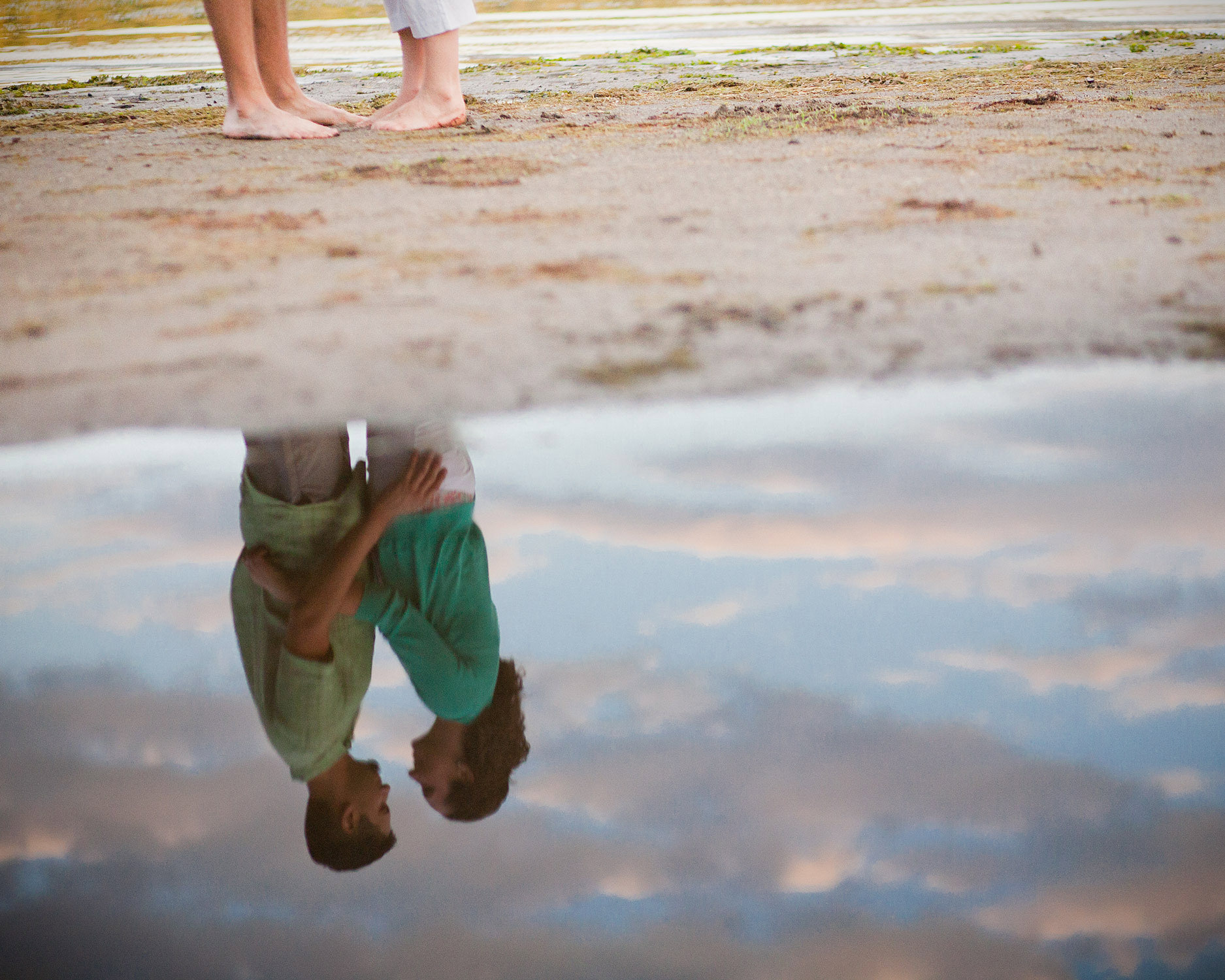Water reflects a posed couple during an engagement session at Niquette Bay State Park in Colchester Vermont