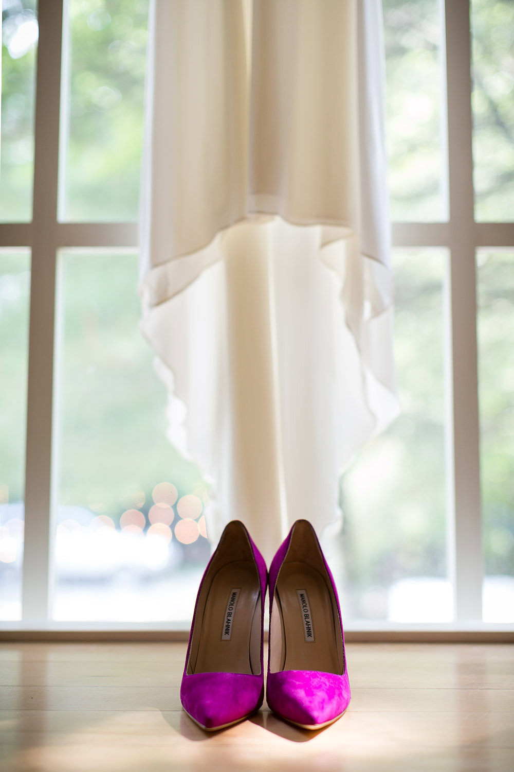 Magenta Manolo Blahnik pumps lined up under a silk wedding dress hung in a window