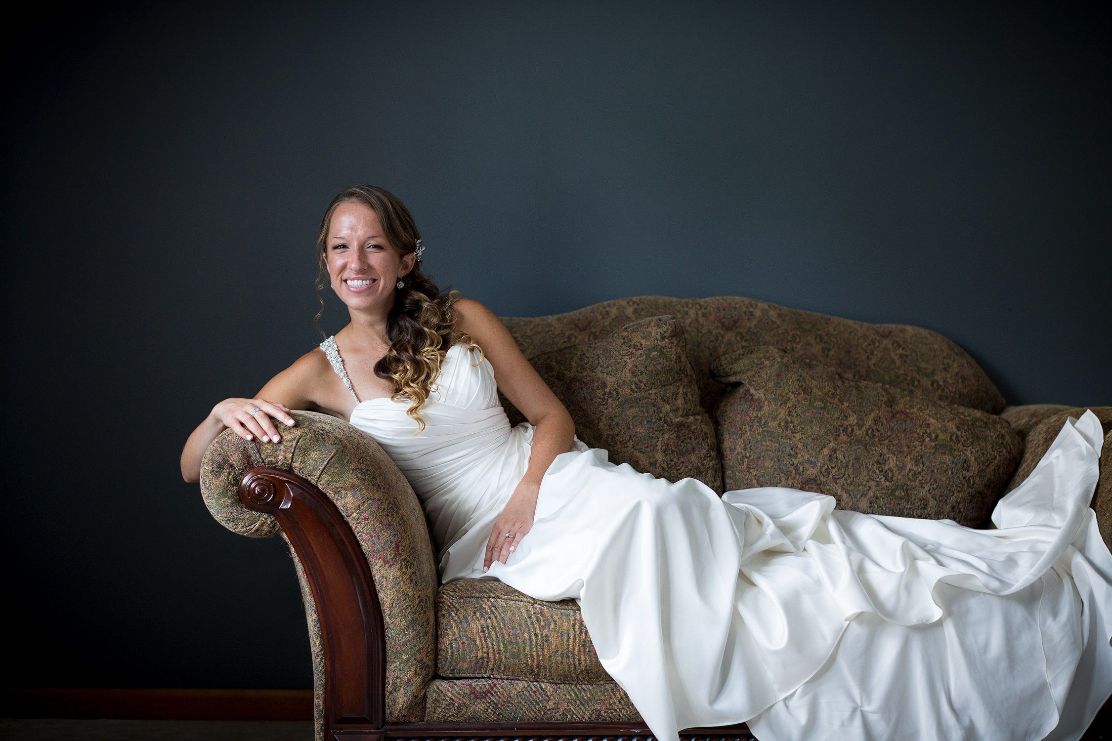 Picture of a bride posing on a couch in a photo by Vermont wedding photographer Stina Booth