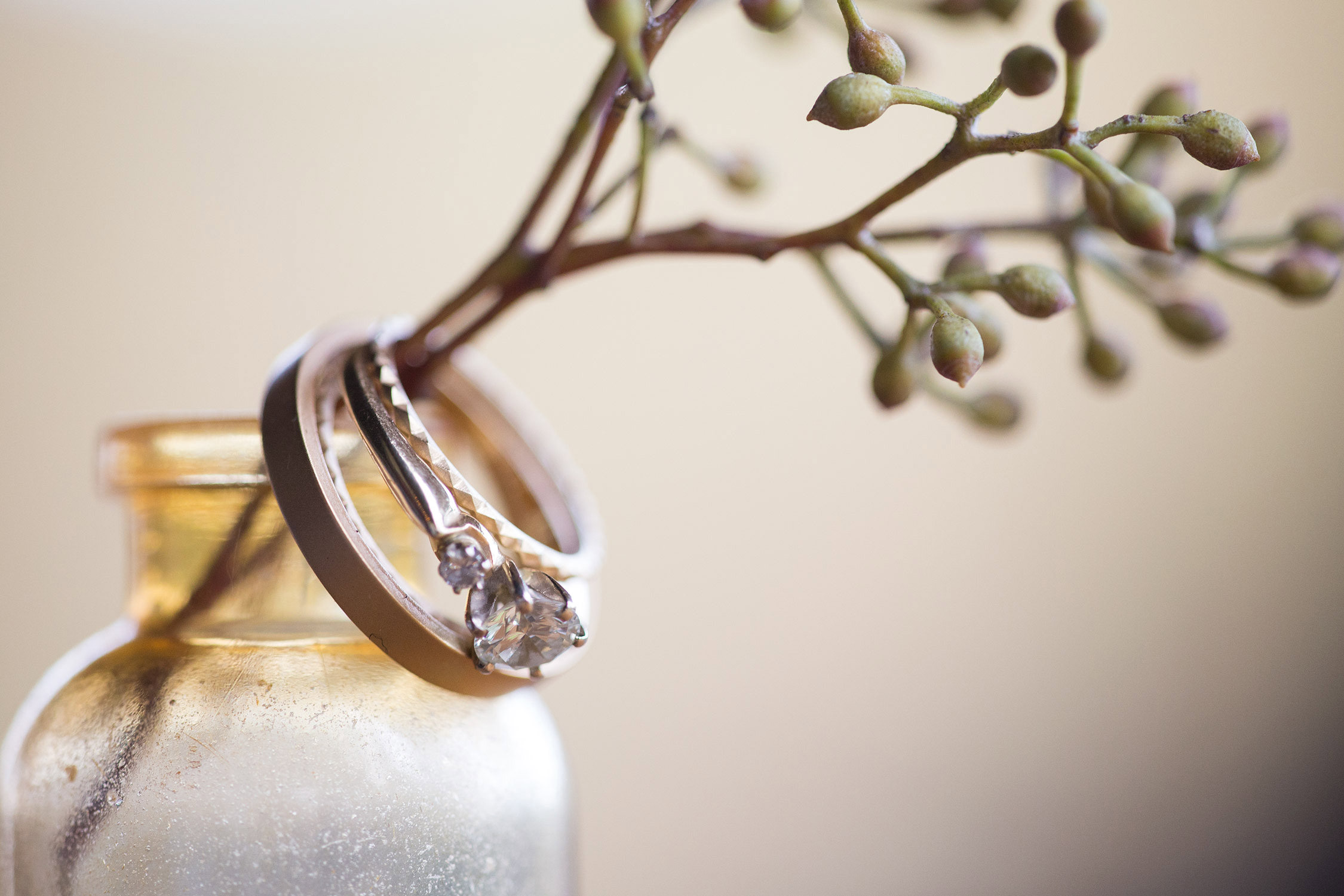 Closeup of wedding rings around a flower stem in a tiny jar