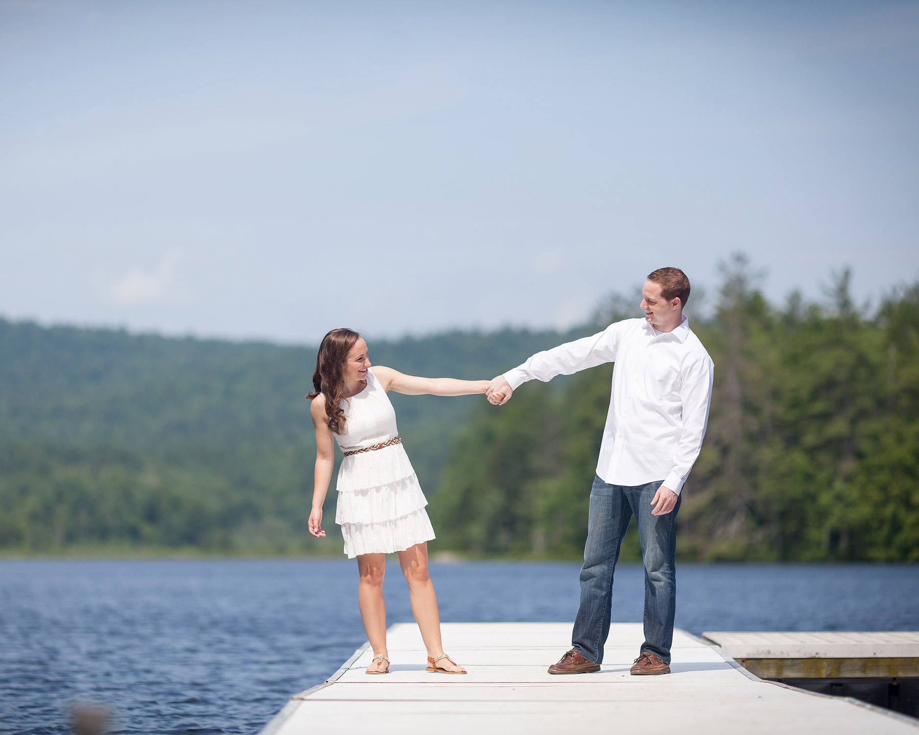 A couple outstretch their arms to hold hands while standing on a dock during a summer camp engagement session