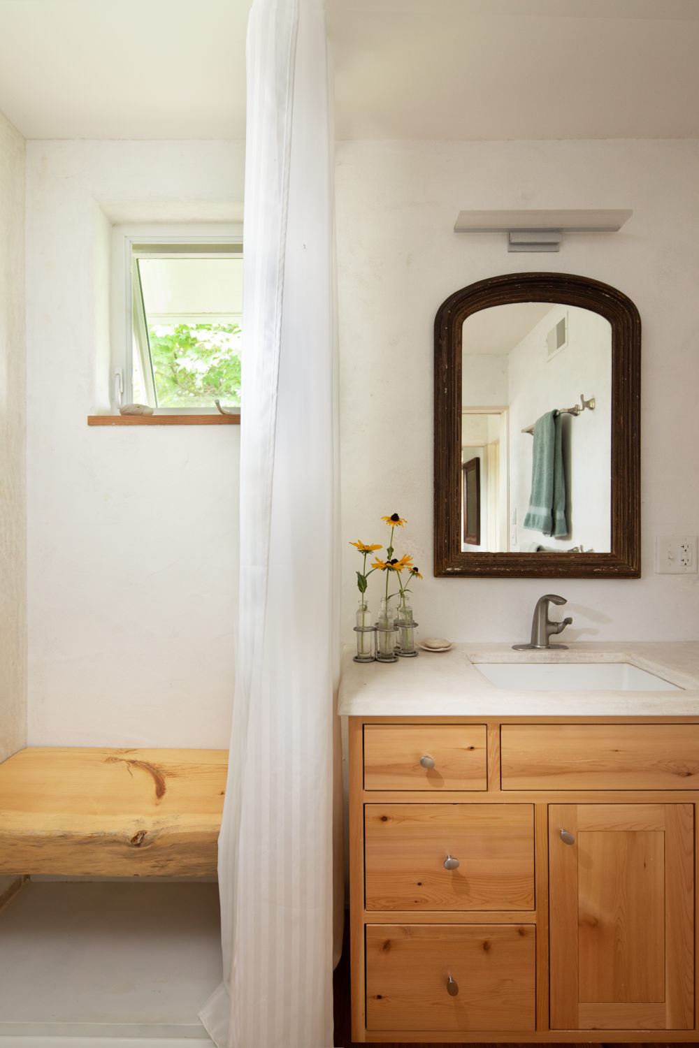 A sustainably retrofitted bathroom with ancient lime plaster walls and tadelakt shower and sink