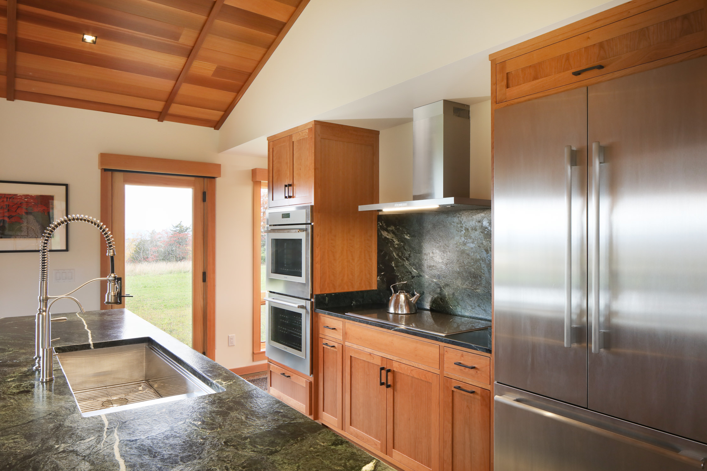 A kitchen with custom wood cabinets in maple finish, stainless steel French door refrigerator and stacked ovens, and Vermont Verde antique stone countertops
