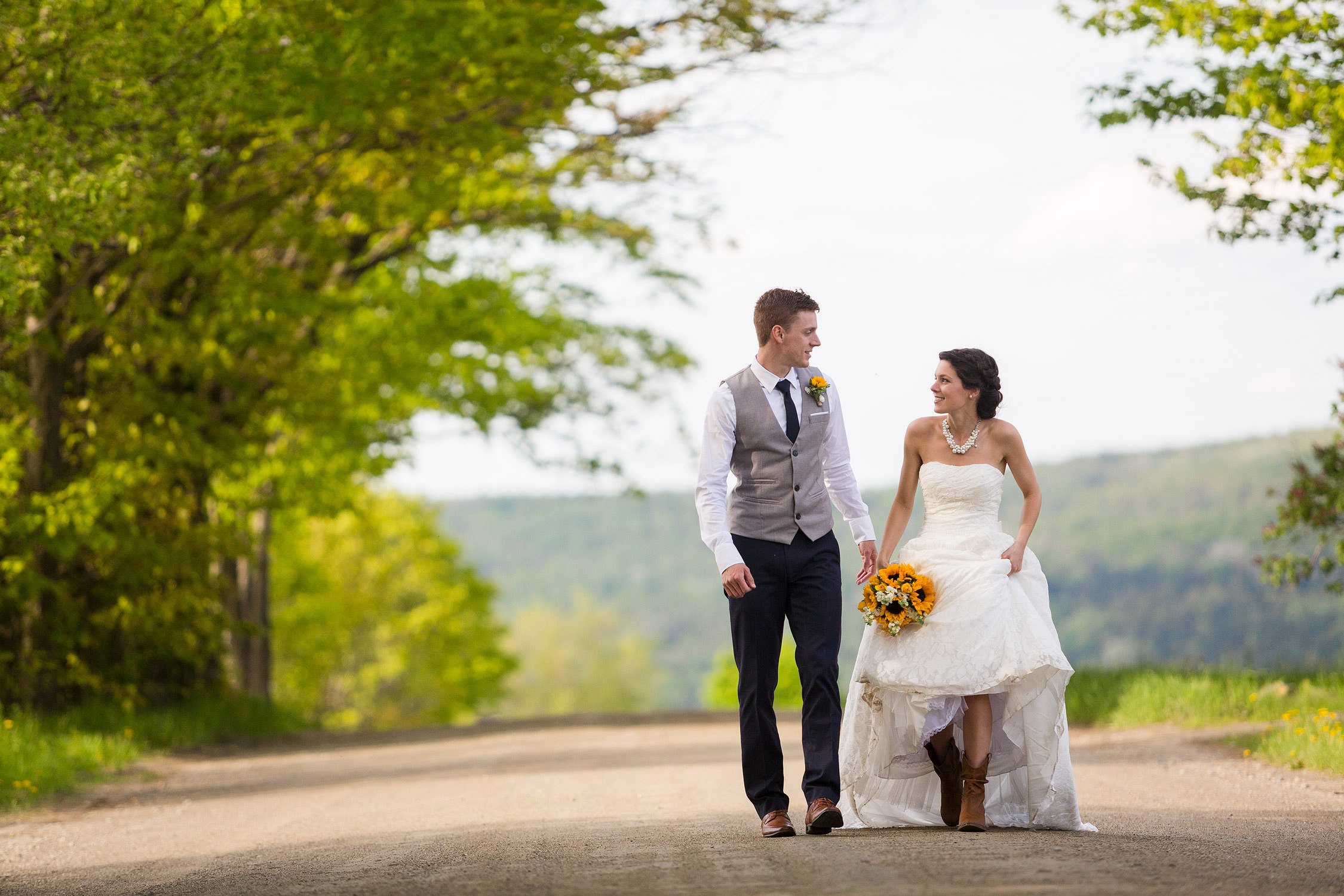 A bride lifts her dress revealing her cowboy boots while walking down a dirt road with the groom in Newport Vermont