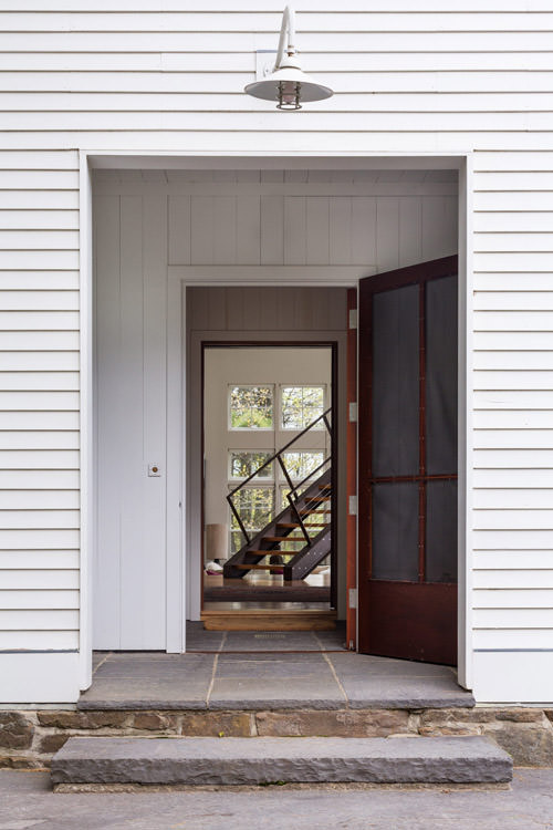 A view through an exterior door into a contemporary home with an industrial steel open staircase by Vermont architecture photographer Stina Booth.
