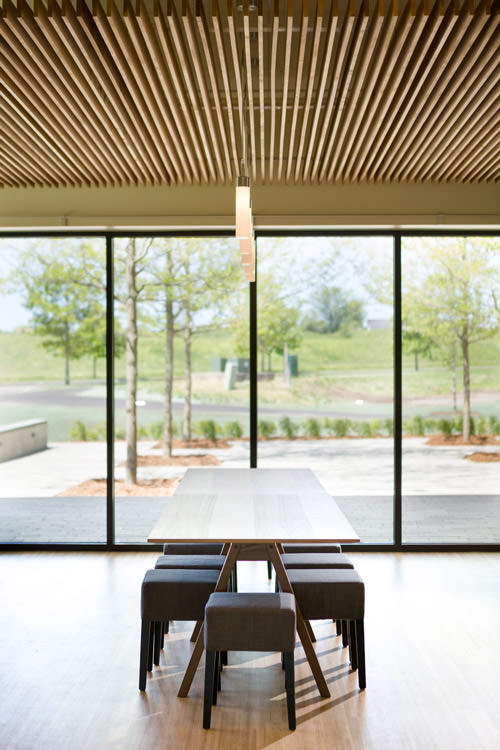 A photo of a long dining table in the Logic Supply cafeteria with modern stools, floor to ceiling windows and a slat wood ceiling with glass light pendants by Vermont architecture photographer Stina Booth.