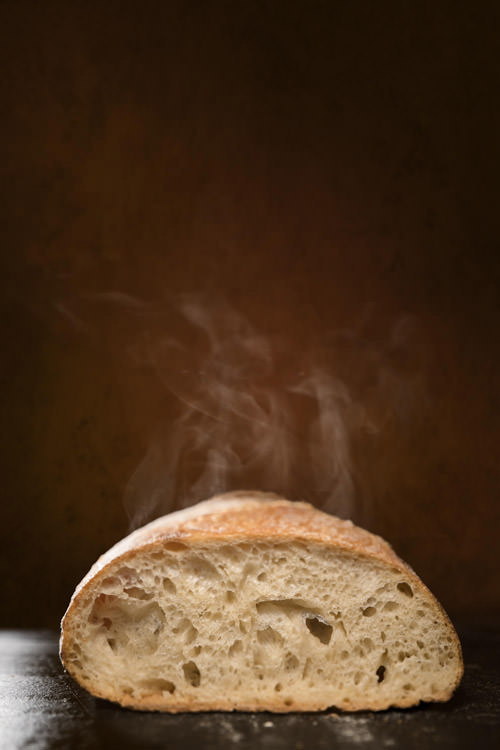 A photo of a steaming loaf of sourdough bread against a dark backdrop by Vermont food photographer Stina Booth.