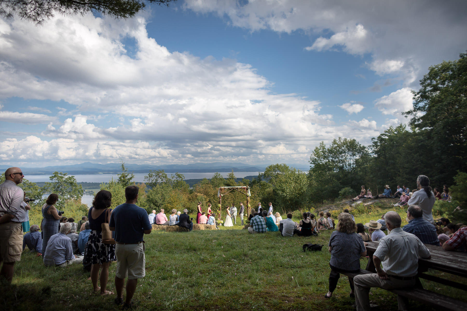 A couple gets married surround by friends on a grassy slope atop Rattlesnake Mountain in upstate New York under blue skies with Lake Champlain and the green mountains of Vermont behind them