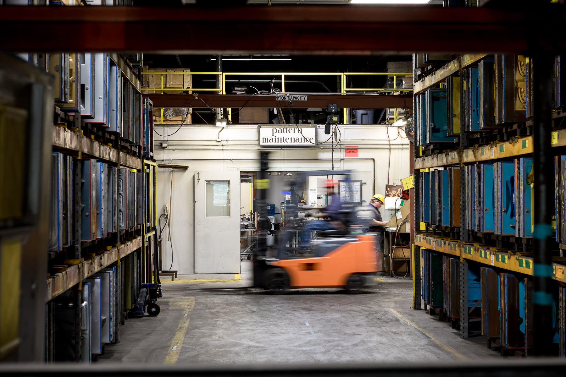 An interior photo of a forklift at work between rows of iron casts in the renovated Vermont Castings manufacturing facility built by Neagley & Chase Construction and photographed by Stina Booth