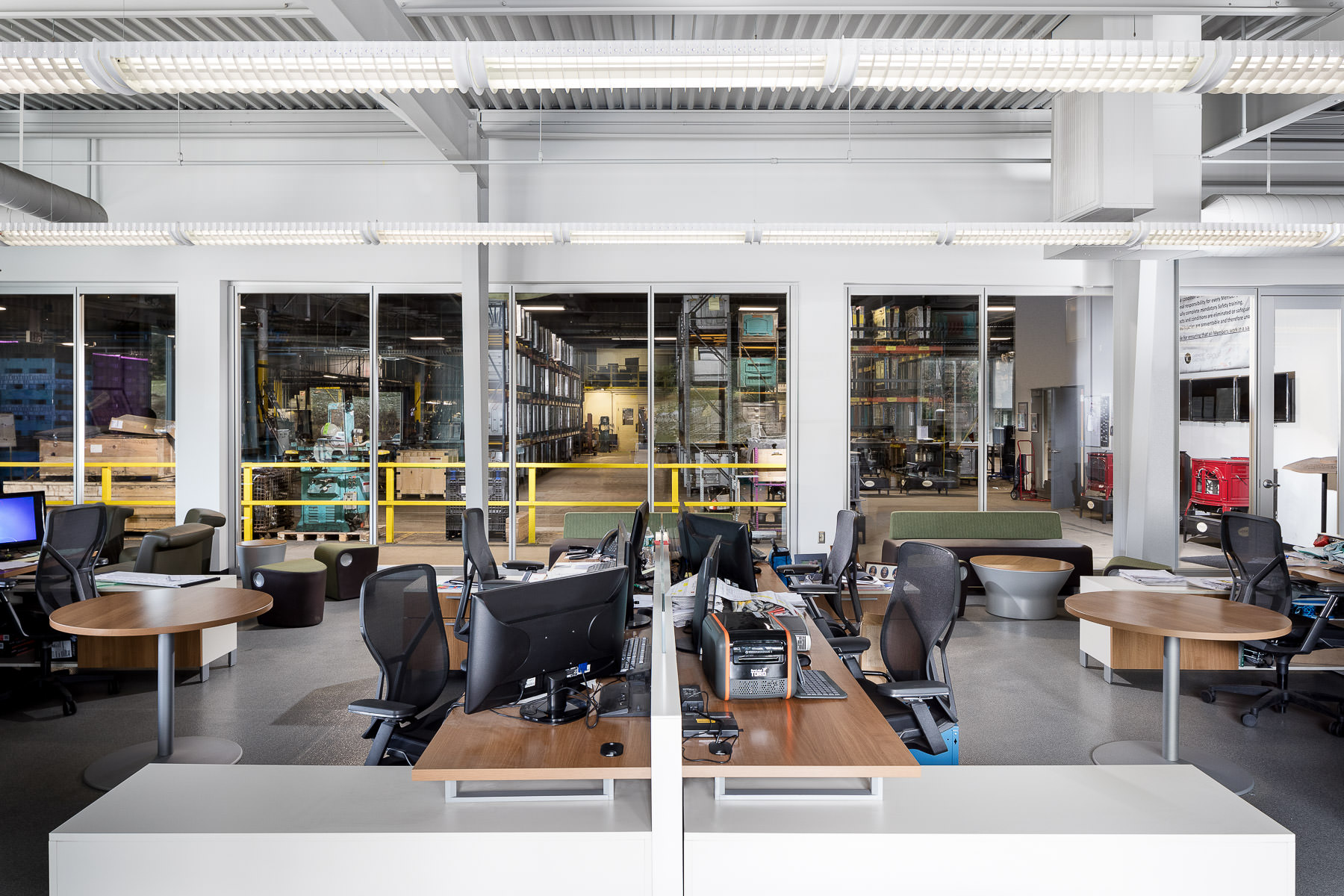 An interior photo of the modern office space with an interior wall of windows at the Vermont Castings manufacturing facility built by Neagley & Chase Construction and photographed by Stina Booth