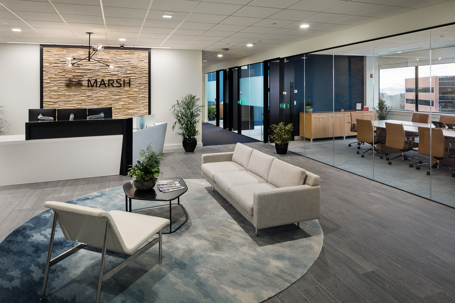 A modern reception area with views into the glass walled conference room at an insurance firm.
