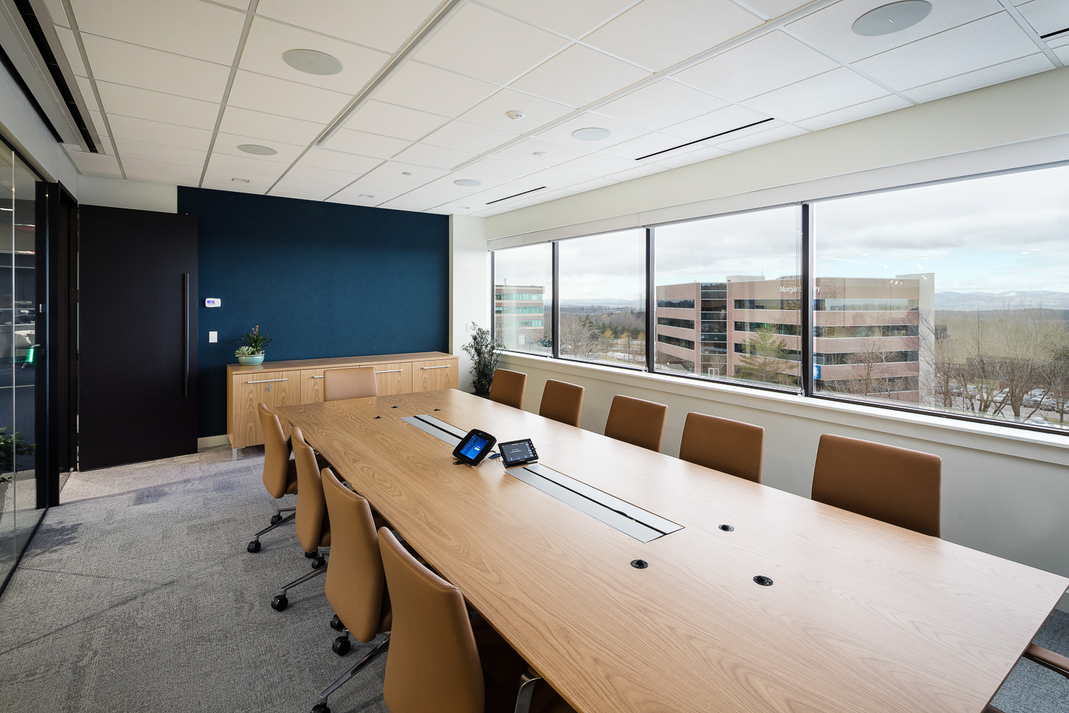 A corporate conference room feels open due to large windows with westerly views of Lake Champlain and glass walls with a view into interior office spaces.