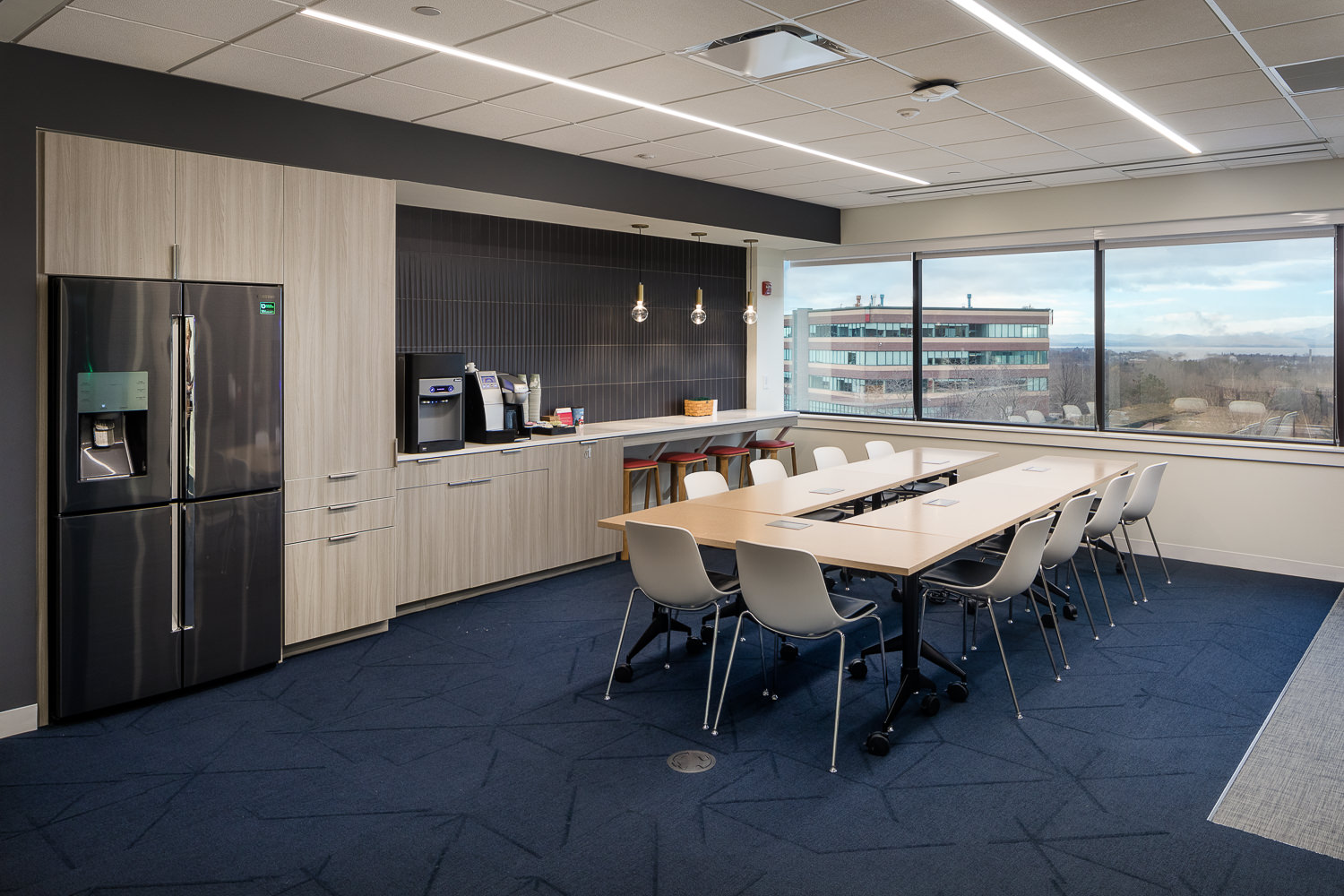 A modern version of a break room includes bar seating, globe pendant lights, and slate-colored vertical wall tiles in a recent renovation of a corporate office space.