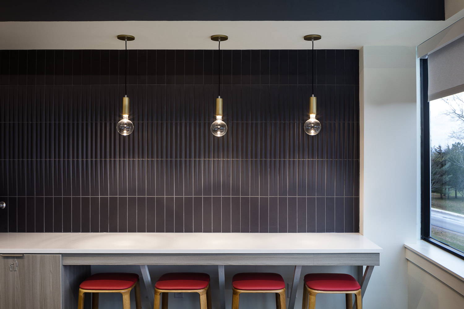 Modern break room seating in a recent corporate office renovation includes bar seating, globe pendant lights, and slate-colored vertical wall tiles.